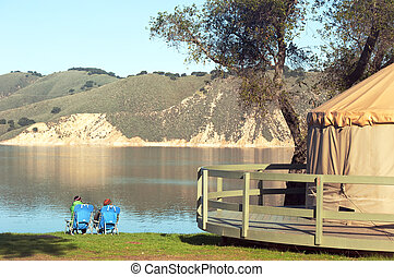 yurt camping - two campers look out onto cachuma lake,...