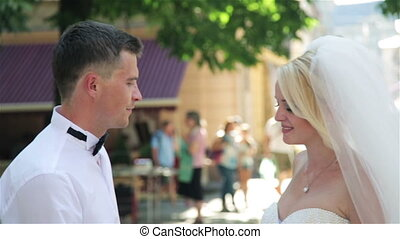 Beautiful wedding couple kissing on the street