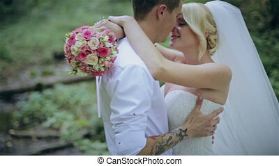 Beautiful wedding couple kissing in a forest HD