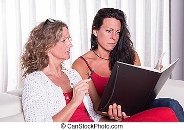 two attractive woman siiting on couch discussing and taking...