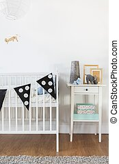 White crib and nightstand in baby room