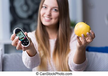 Holding glucometer and apple - Young diabetic woman holding...