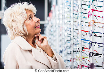 Senior woman searching for glasses - Image of senior woman...
