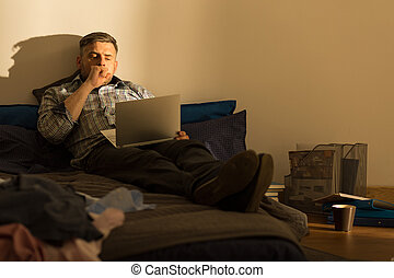 Yawning man on bed - Tired man sitting on bed with laptop
