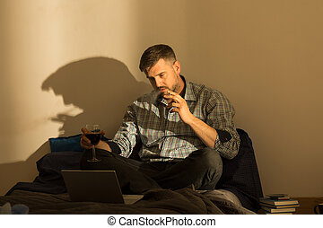 Smoking man on bed - Smoking man sitting on bed with laptop
