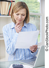 Concerned Woman Reading Letter In Home Office