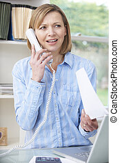 Woman On Telephone In Home Office