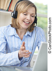 Middle Aged Woman Talking Online Using Headset