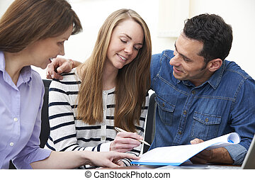 Couple With Financial Advisor Signing Document In Office