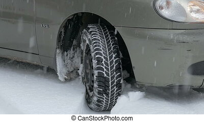 wheel slip on snow - view of the wheel while driving on a...