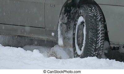 Car tires on winter road - view of the wheel while driving...