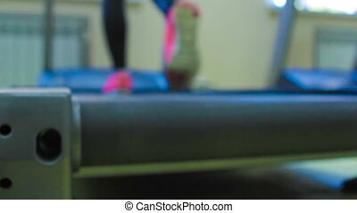 Close up woman's legs in pink sneakers on a treadmill. Left rear view.