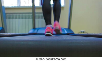 Close up woman's legs in pink sneakers on a treadmill. Back view.