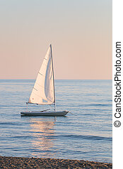 small sailboat in the water anchored next to the beach in a...