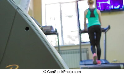 back view on slim woman running in gym on treadmill Slider...