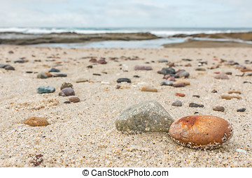 Small rocks scattered on beach sand close up - Shallow depth...