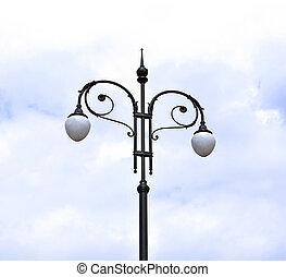 Old lantern - Old streetlight on the cloudy sky background