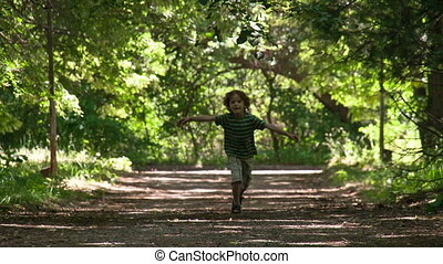 Sweet Childhood - A little boy runs towards the green shaded...