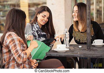Group of women taking a break from shopping - Three cute...