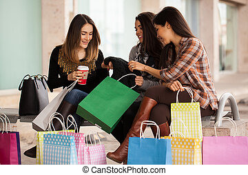 Female friends after a shopping spree - Three women taking a...