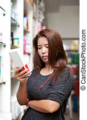 asian woman buying medicine at pharmacy store