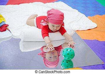 Cute five months asian baby playing ball on mirror in...