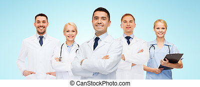 group of smiling doctors with clipboard - medicine,...