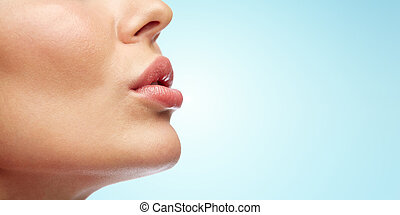 close up of young woman lips over blue - beauty, people,...