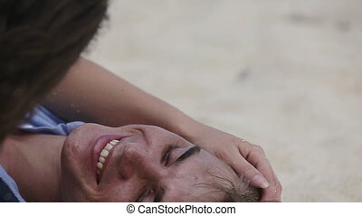 Lovers lying down on the beach - Happy couple lying on a...