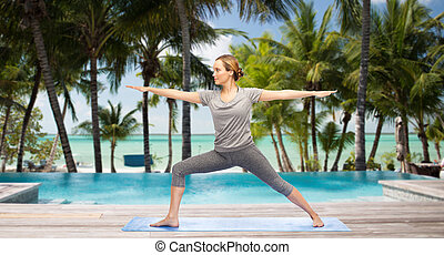 woman making yoga warrior pose over hotel resort - fitness,...