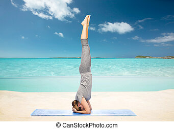 woman making yoga in headstand pose on beach - fitness,...