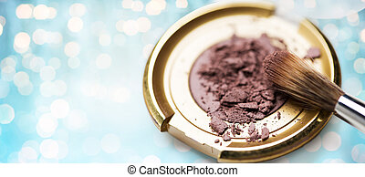 close up of makeup brush and eyeshadow over lights -...