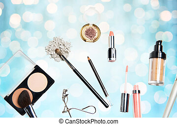 close up of makeup stuff over blue lights - cosmetics,...