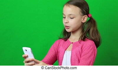 Emotional little girl talking on Skype at phone - Emotional...