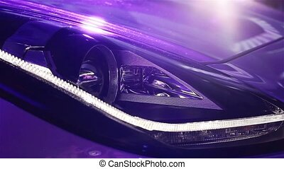Headlight of supercar in neon lights. Jaguar