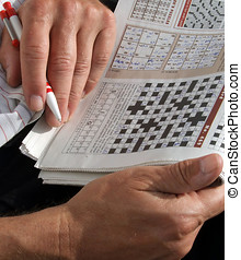 Quiz Games - Male filling out puzzles in the newspaper