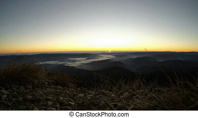 Sunrise panorama over the misty valley