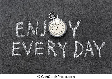 enjoy every day phrase handwritten on chalkboard with...