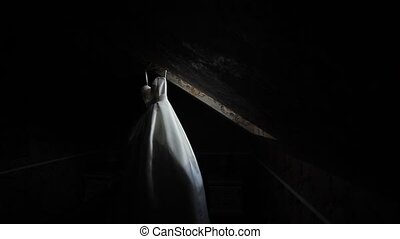 Wedding dress hanging in dark room - A white wedding dress...
