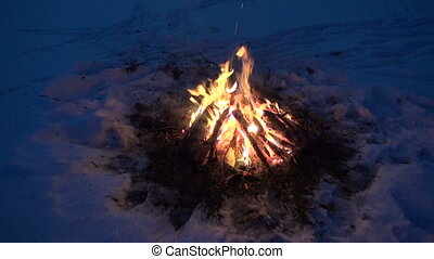 Bonfire burning in the snow - Bonfire campfire burning...