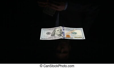 an unidentified man takes dollars from the black table some...