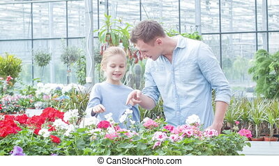 Father and daughter choosing the flowers. - Selecting a...