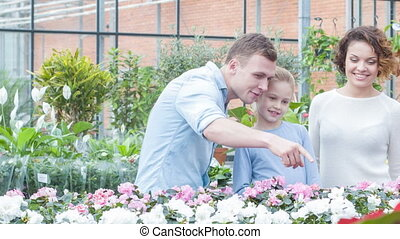 Young family choosing flowers in the greenhouse.