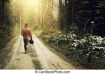 Nature footpath through snowy forest and walking alone man against fog and sunshine