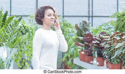 Young woman having a phone talk in the greenhouse.