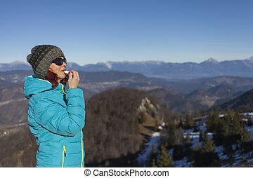 Woman trekker applying balsam lips - Pretty mid aged woman...