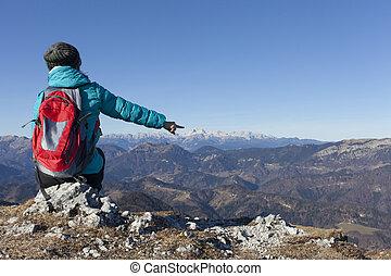 Trekker pointing on Mount Triglav - Trekker with backpack...