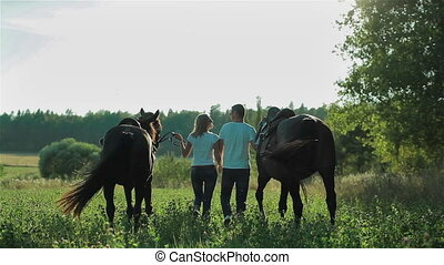 Happy young couple with horses