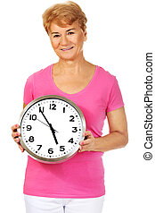 Smiling senior woman holding a clock