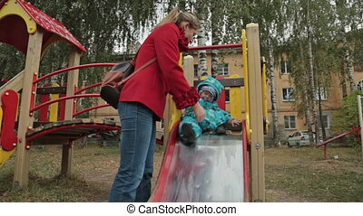 Little boy sliding at playground with him mother